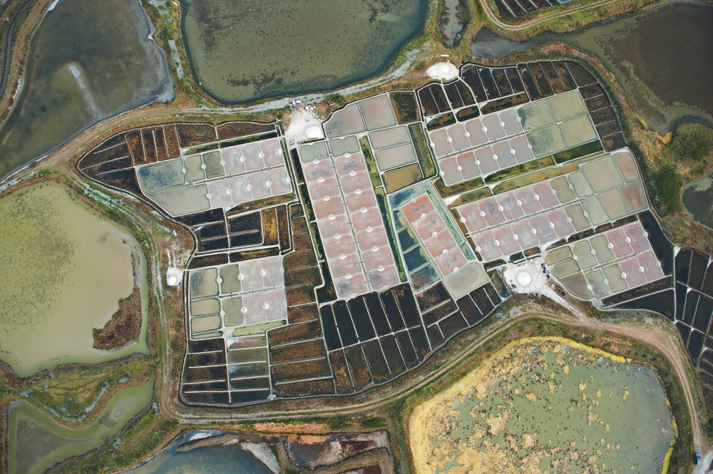In die etwa 300 Salzgärten im französischen Guérande lassen die Bauern bei Flut Meerwasser einströmen. Das Wasser durchläuft lange Kanäle und mehrere Becken, damit es sich immer mehr konzentriert und schließlich in flachen Verdunstungspfannen kristallisiert. (Foto: © Mikel Landa / Landa-Ochandiano arquitectos)