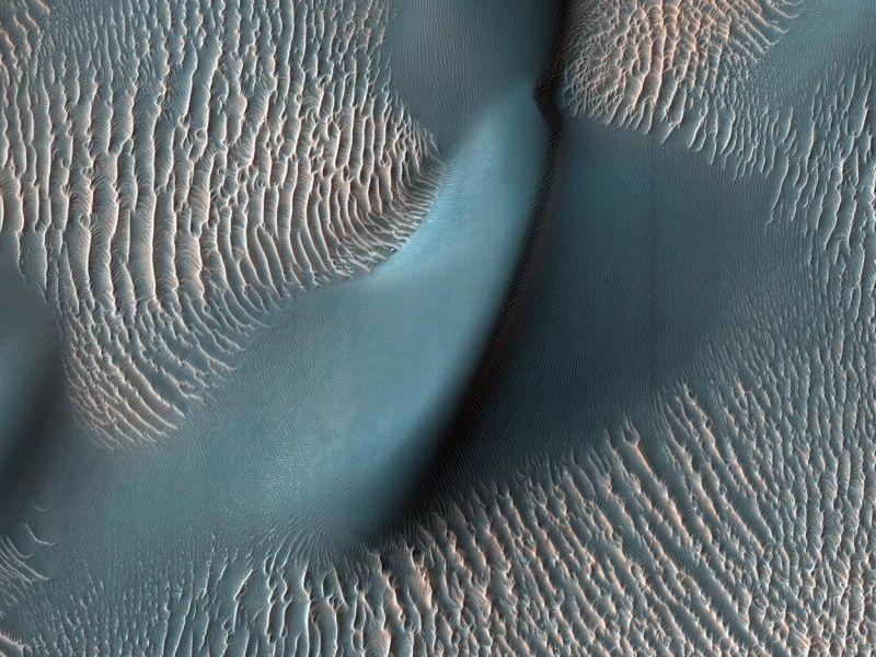 Dieses Foto zeigt eine große Marsdüne umgeben von vielen Sandrippen. Sie demonstrieren, wie der Wind die Oberfläche des Planeten formt. Die blaue Farbe wurde gewählt, um die Dünnen und Wellen der Oberfläche zu verdeutlichen. (Bild ©  NASA/JPL-Caltech/University of Arizona)