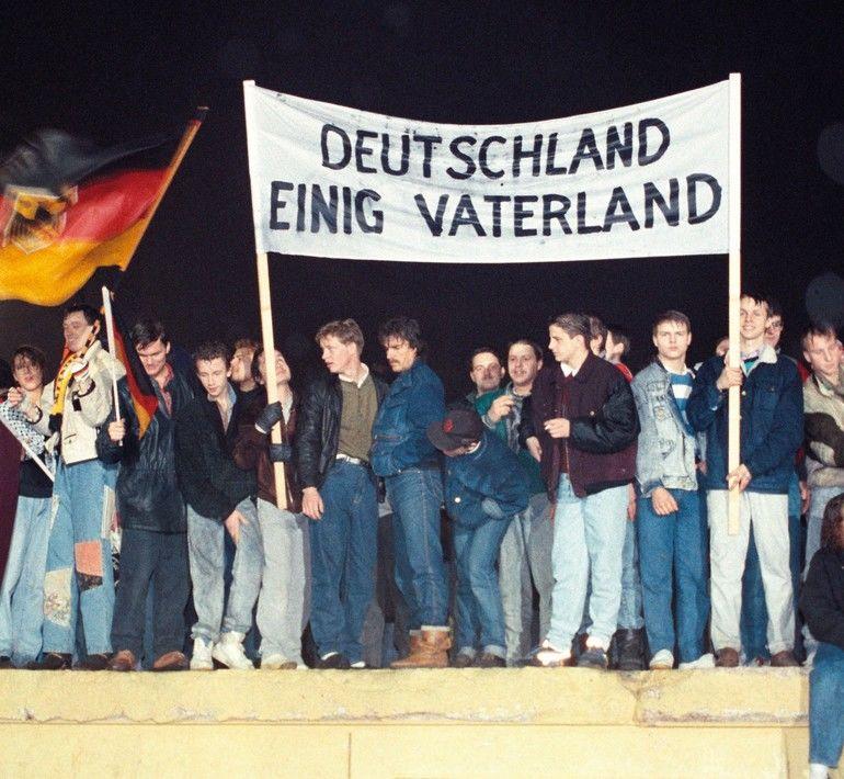 Mit_der_Deutschlandfahne_und_einem_Transparent_Deutschland_Einig_Vaterland_stehen_zahlreiche_Berliner_am_22.12.1989_auf_der_Berliner_Mauer_am_Brandenburger_Tor._Das_Tor_ist_seit_diesem_Tag_–_28_Jahre_nach_dem_Mauerbau_–_wieder_zugänglich._Der_Untergang_de