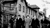 The_group_of_the_Frankfurt_jury_court_and_several_journalists_are_passing_the_camp_gate_with_the_words_'Arbeit_macht_frei'_(work_brings_freedom)._The_first_local_inspection_during_the_Auschwitz_Trial_took_place_on_the_grounds_of_the_former_concentration_c