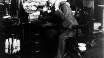 ._Thomas_Alva_Edison_at_his_desk,_talking_on_telephone,_on_1914_Sept._8._An_Edison_wax_cylinder_dictating_machine_is_seen_to_the_left_with_several_cylinder_records_beneath_it._On_floor_to_right_of_Edison's_chair_is_a_spittoon_and_a_metal_wire_waste-basket