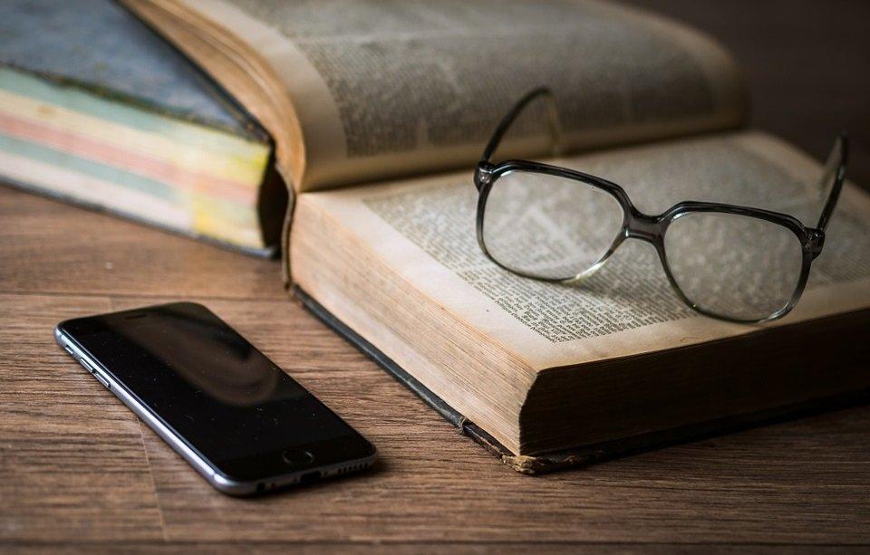 Smartphone neben aufgeschlagenem Buch