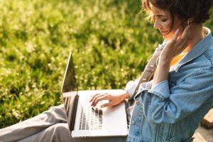 Junge Frau mit Laptop auf einer Parkbank