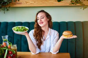 Junge Frau mit Salatschale und Burger in den Händen