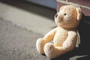 Teddybär, an Mauer lehnend
