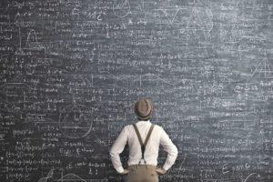 Mann vor einer Wandtafel voller mathematischer Formeln